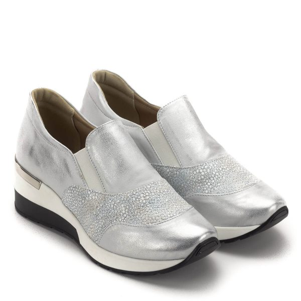 Carla Ricci cipő vastag gumi talppal ezüst színben. A cipő orrán és oldalában strukturált bőr betét található, sarokrészén fém díszítő elem kapott helyet. Ez a telitalpú Carla Ricci cipő kívül belül bőrből készült, az elejében található gumi betétnek köszönhetően magasabb lábfejre is passzol. Kényelmes, puha női cipő.