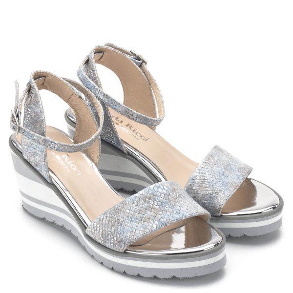 Carla Ricci szandál ezüst-kék színben, 7 cm magas sarokkal. Talpa 2 cm vastag, kényelmes bokapántos telitalpú szandál. Anyaga kívül-belül bőr.